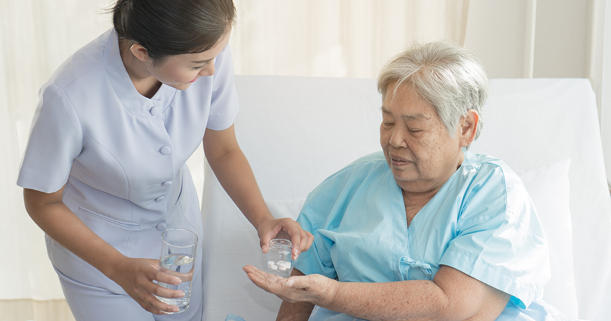 Prescribing nurse assisting patient with medication