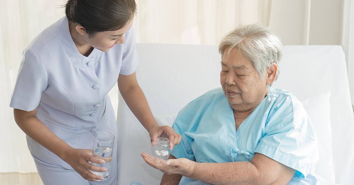 Prescribing nurse assisting patient with medication