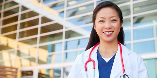 smiling female doctor outside hospital